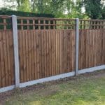 Closeboard panels, with trellis, erected on slotted posts.