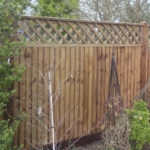 Closeboard fencing, with diamond trellis, erected on wooden posts.