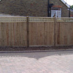 Closeboard fencing, with square trellis, erected on wooden posts.