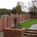 Closeboard panels fencing, erected on slotted posts.